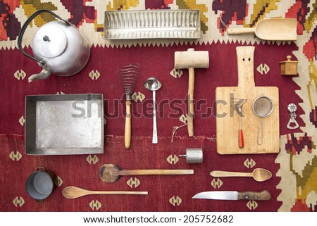 Old kitchen utensils on an old carpet - stock photo