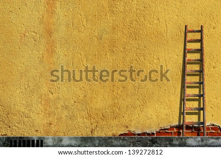 Old ladders on blank yellow wall - stock photo