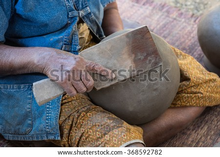 Old lady crafting clay pot for traditional living background with selective focused point - stock photo