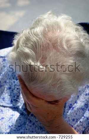 old lady crying holding her face with her hand - stock photo