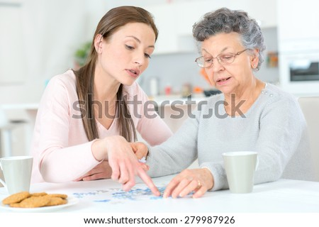 Old lady doing a jigsaw puzzle - stock photo
