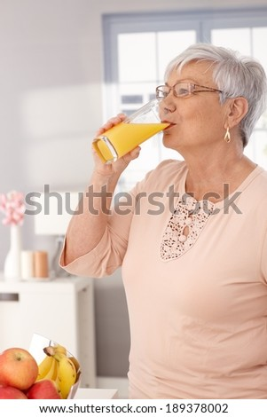 Old lady drinking orange juice in the morning. - stock photo