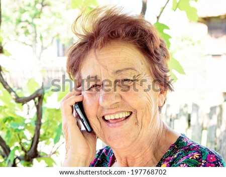 Old lady using mobile phone and have smile on her face - stock photo
