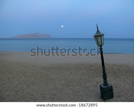 Old lamp on the empty, night beach with the Moon and island on the horizon