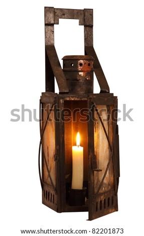 Old lamp with burning candle, isolated on white background - stock photo