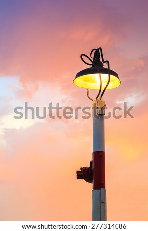 old lamps shining in sunset sky - stock photo