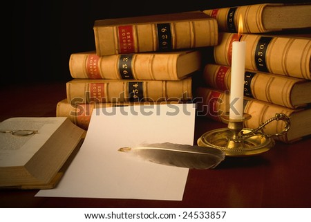 Old law reports, glasses, candle and quill.