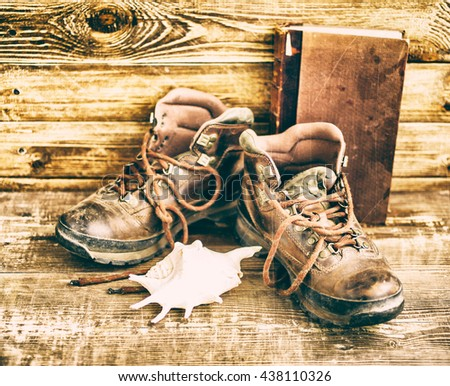 Old leather boots. Boots on a wooden background. Vintage toning. Travel composition.  - stock photo