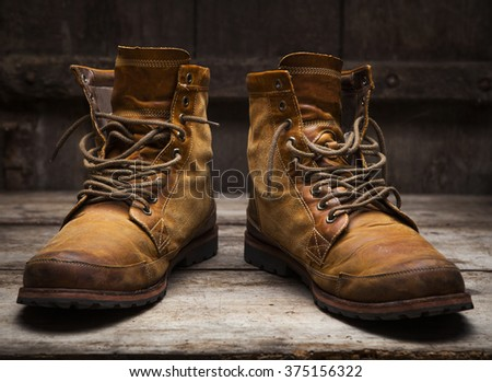 Old leather shoes on wooden background - stock photo