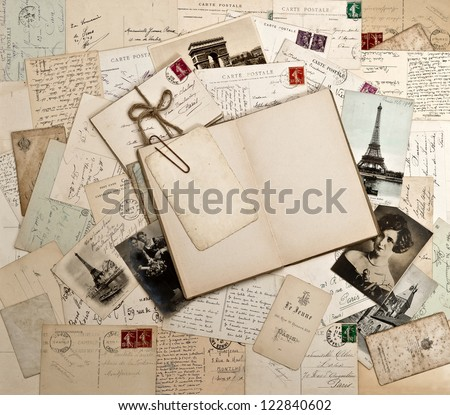 old letters, french post cards and empty open diary book. nostalgic vintage background