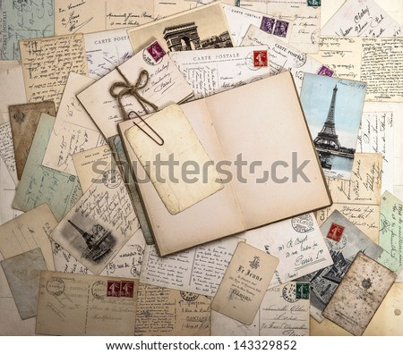 old letters, french postcards and empty open book. nostalgic vintage background