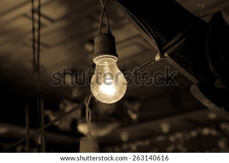 Old light bulb glowing. Vintage filter. - stock photo