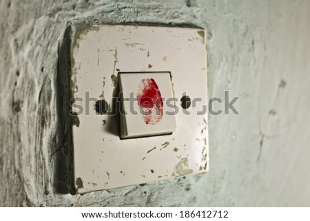 Old light switch on old cracked green wall with bloody fingerprint on it - stock photo