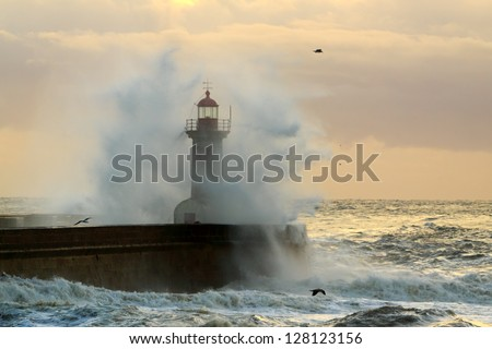 Old lighthouse of the entry of the harbor of river Douro during a winter storm sunset - stock photo