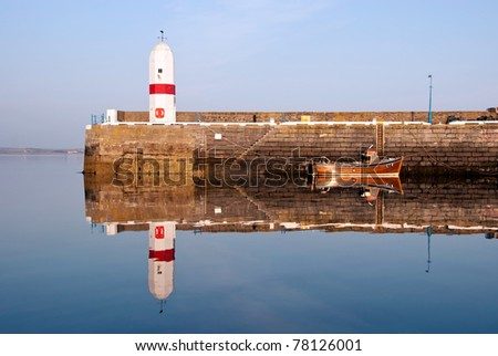 Old Lighthouse on Breakwater Wall in a Harbour with Boat. Sea and Bright Blue sky. Water Reflection. Isle of Man
