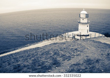 Old lighthouse on top of rock against sea with round horizon. Fisheye view, filtered toned image. - stock photo