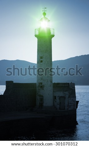 Old lighthouse tower silhouette on the coast of Mediterranean Sea, green light. Blue toned, stylized night photo - stock photo
