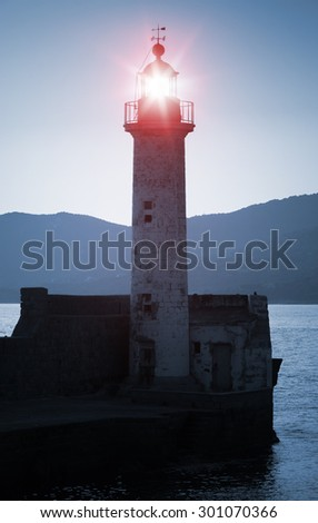Old lighthouse tower silhouette on the coast of Mediterranean Sea, red light. Blue toned, stylized night photo