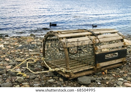 Old Lobster Trap: old handmade wooden lobster trap on pebble beach in the Maritime Provinces of Canada - stock photo