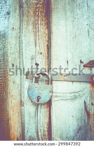 Old lock on the door. lock on the door of an old farmhouse . true village style . close-up. focus on lock. retro style toned photo - stock photo