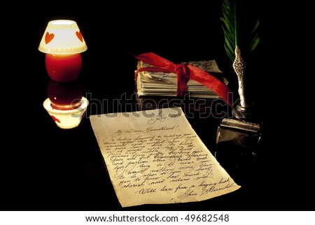 Old love letter, antique quill, stack of letters tied with a red ribbon and romantic candle - stock photo