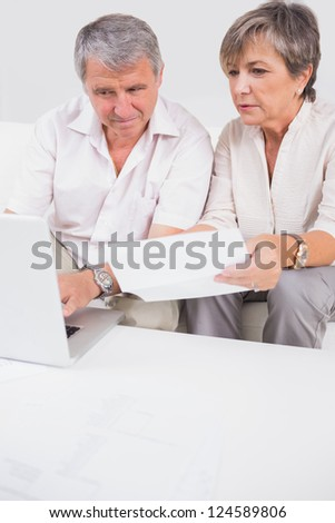 Old lovers not understanding the accounts and using laptop in sitting room - stock photo