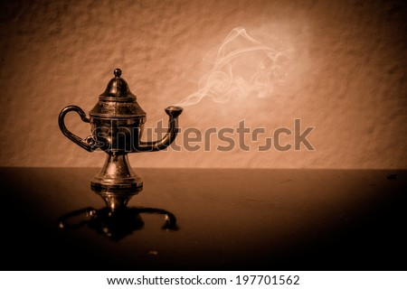 Old magic lamp on a table - stock photo