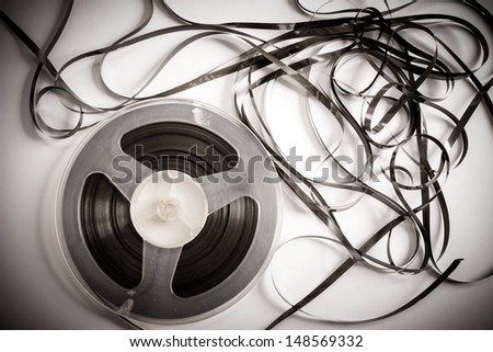 Old magnetic tape reel with loose tape  - stock photo