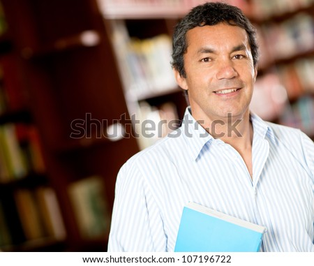 Old male university student smiling at the library - stock photo