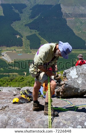 Old man adjust gear for rope climbing - and majestic mountain landscape as a background. Shot in Jonkershoek nature reserve, Stellenbosch, Western Cape, South Africa. - stock photo