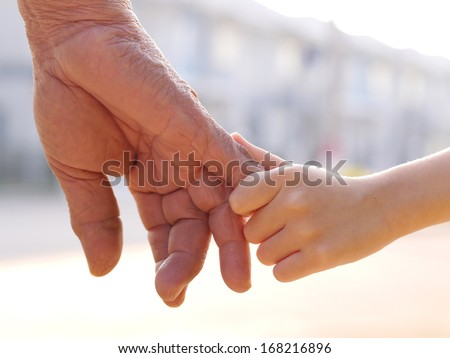 old man and a kid holding hands together - stock photo