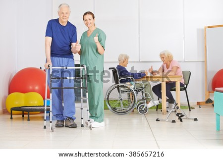 Old man and geriatric nurse holding thumbs up together in a nursing home - stock photo
