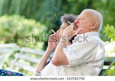 Old man and woman smoking