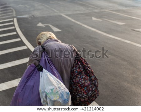 Old man carry belonging walk beside the street. Depressed and loneliness concept. - stock photo