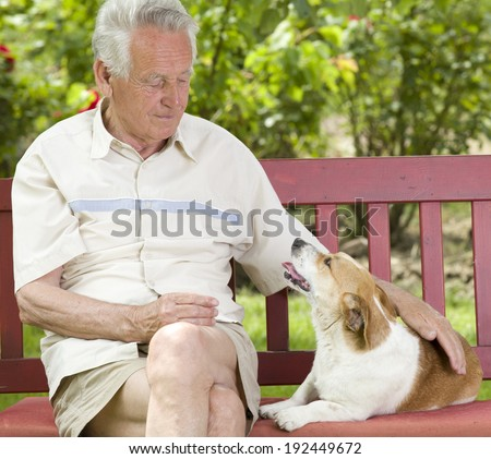 Old man cuddling his dog on bench in garden - stock photo