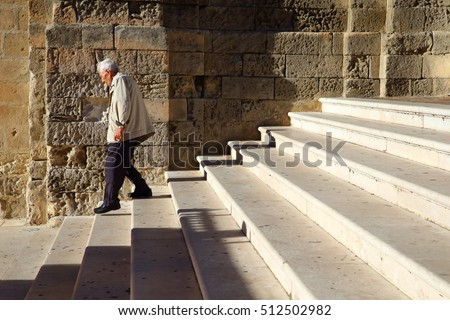 old man descending some stairs/ senior/ senior man descending stairs with walking stick
