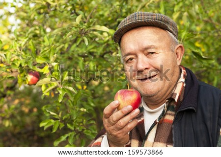 old man eating a ripe apple