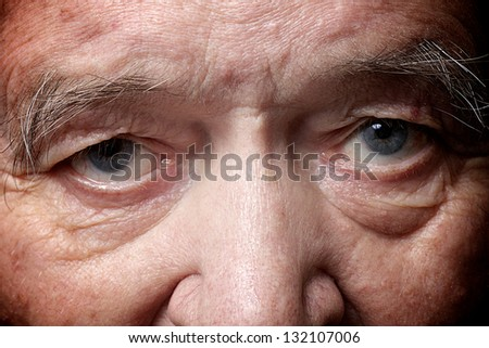 old man face part closeup eyes looks at camera - stock photo