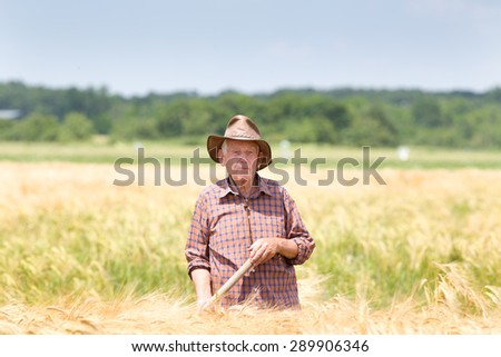 Old man farmer resting in barley field after hard work - stock photo