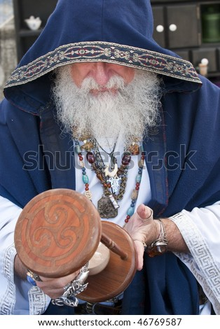 Old man, fortune teller looking at hour glass. - stock photo