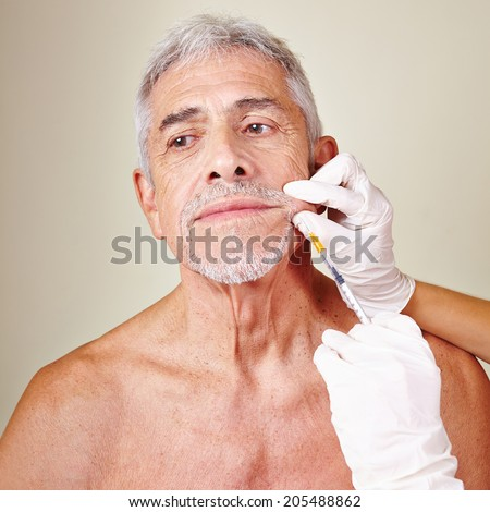 Old man getting wrinkle treatment with hyaluronic acid in beauty parlor - stock photo