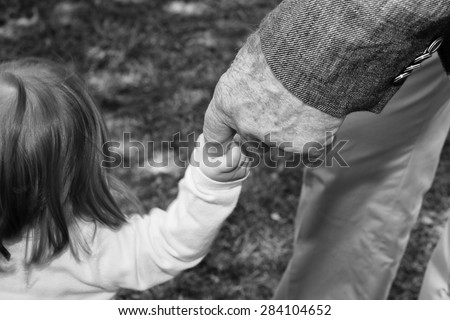 old man hand while holding newborn infant in black and white - stock photo