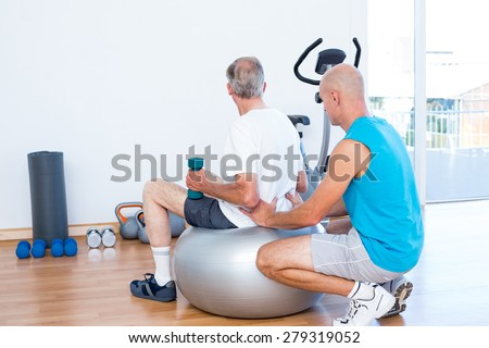old man having back massage on exercise ball in medical office - stock photo