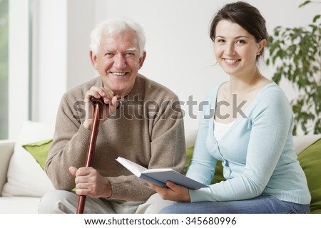 Old man holding cane and young woman reading a book - stock photo
