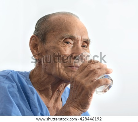 Old man holds and drinks glass of water