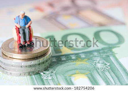 Old man in a wheelchair with money / wheelchair user - stock photo