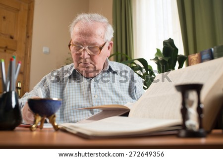 Old man in glasses writing from the books in the room. Close portrait
