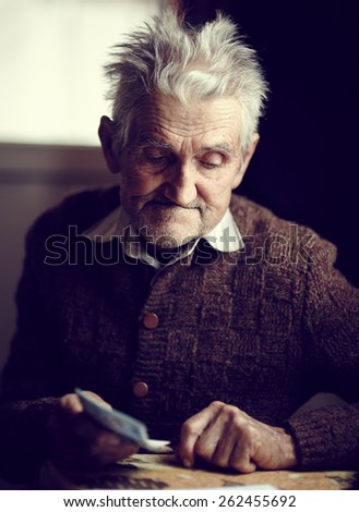 Old man in his 80s having just received his small pension, with a pensive expression on his face - stock photo