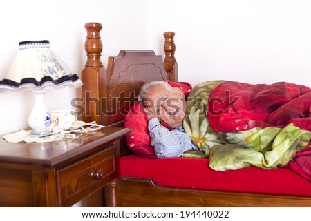 Old man laying in his bed and suffering from insomnia - stock photo