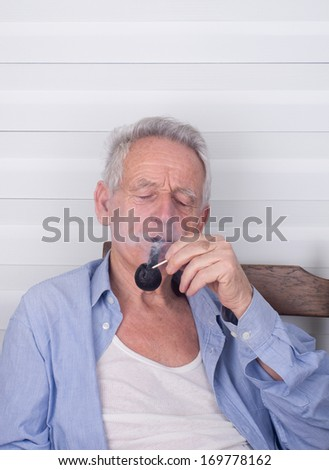 Old man lighting up smoking pipe with matches - stock photo